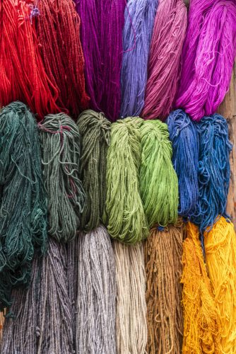 Naturally dyed alpaca wool hanging on a drying rack