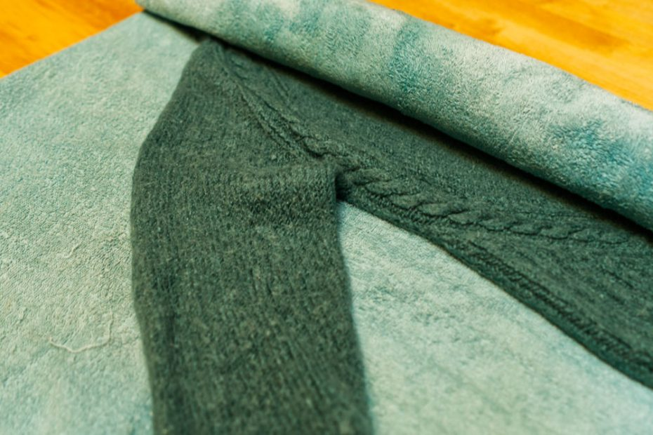 Rolling your jumper in a towel helps to gently squeeze excess water out of it